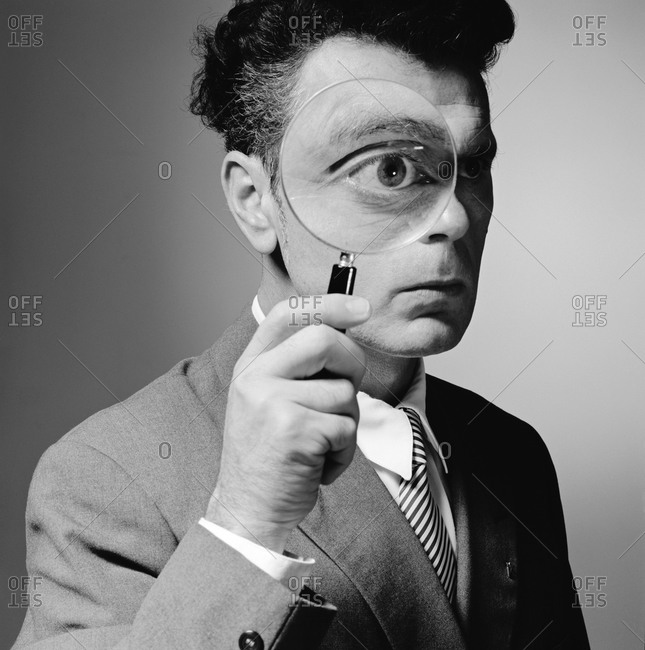 A man holds a magnifying glass in front of his eye