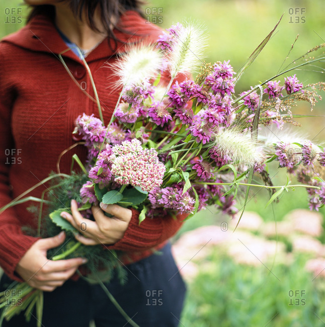 A woman holds a bouquet of purple flowers
