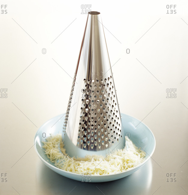A cone shaped grater with shredded cheese