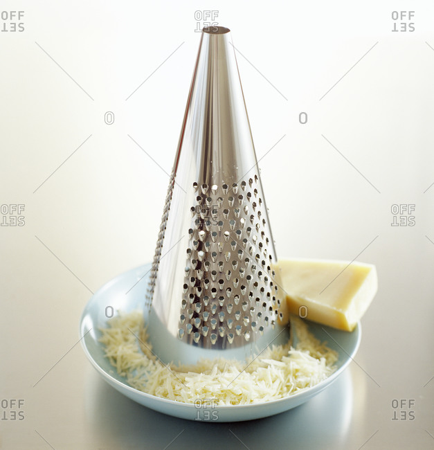 A cone shaped grater with a block of parmesan