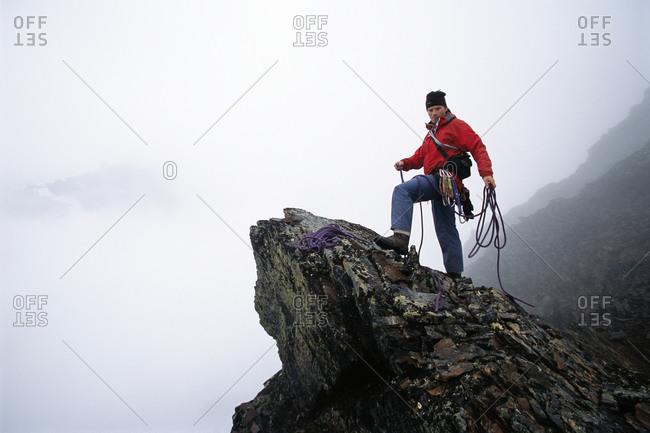 A mountain climber on a foggy mountain top