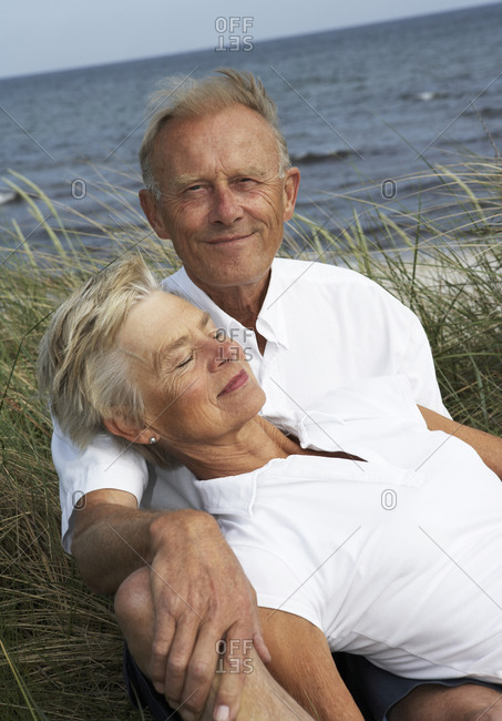 An older couple relaxes by the shore