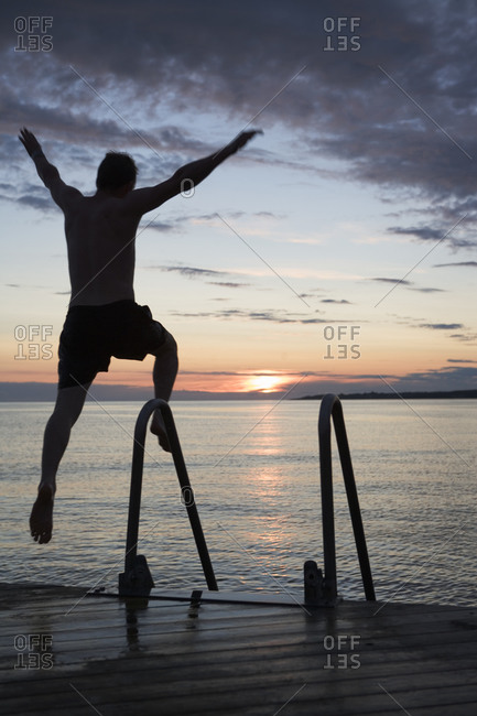 A man jumps into the ocean at sunset in Skane, Sweden