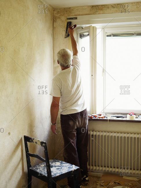 A handyman repairs walls in Stockholm, Sweden