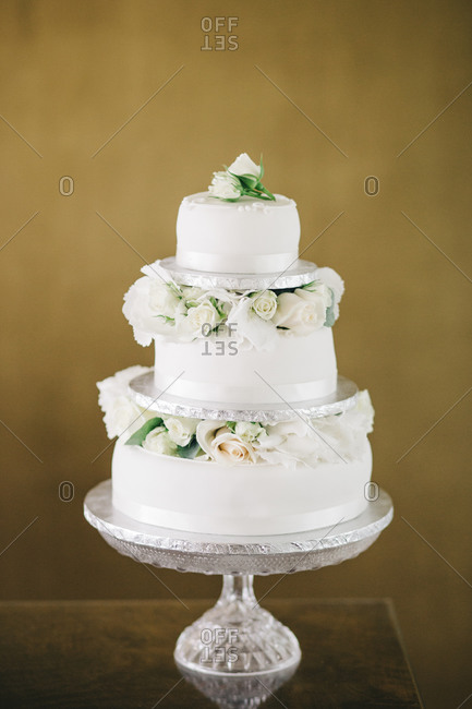 Three-tiered wedding cake with white roses