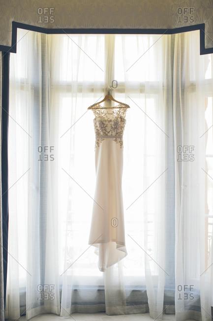 Wedding dress hanging by the window