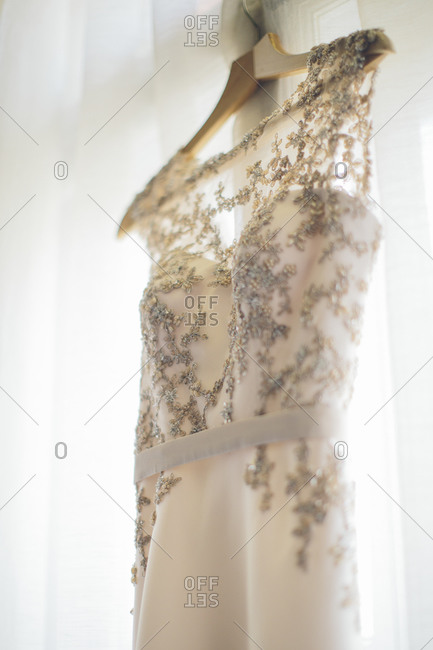 Elegant wedding dress hanging by the window