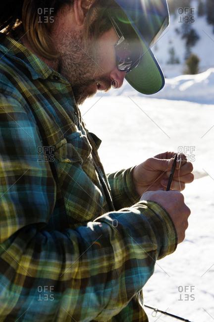 Man tying fishing lure outdoors