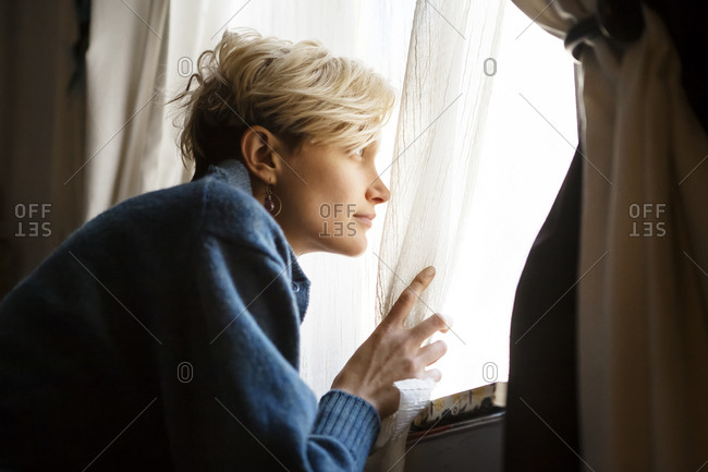 A young woman anxiously looks out a window