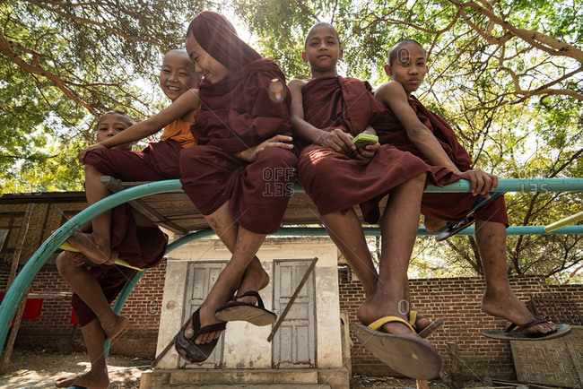 Mandalay, Myanmar - March 1, 2015: Group of young monks sitting on monkey bars