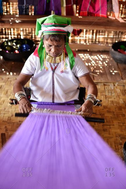 Inle Lake, Myanmar - March 3, 2015: Kayan woman working on a loom in Myanmar