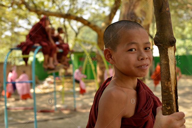 Province of Mandalay, Myanmar - March 1, 2015: Portrait of a young monk at a playground