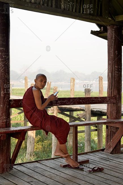 Amarapura, Mandalay, Myanmar - March 1, 2015: Young monk using a cell phone at the U Bein bridge in Myanmar