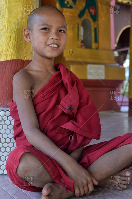 Amarapura, Mandalay, Myanmar - February 28, 2015: Young Buddhist monk sitting at a temple in Myanmar