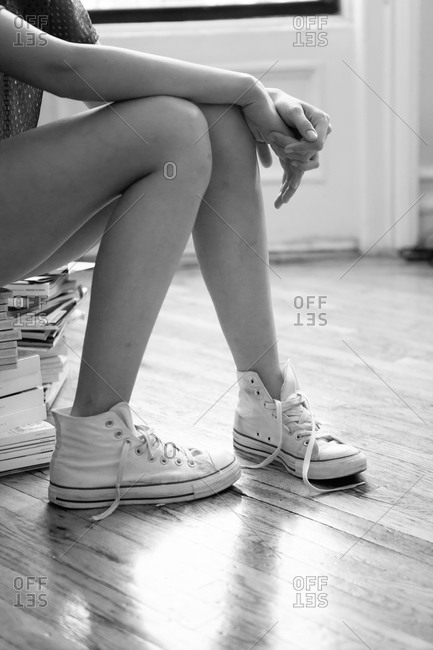 Young woman wearing high-top sneakers sitting on stack of books