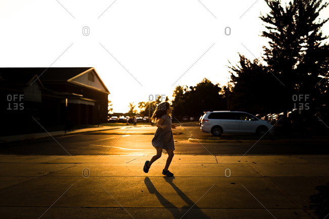 Child running in a street at sunset