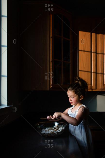 Girl mixing mini marshmallows chocolate chips