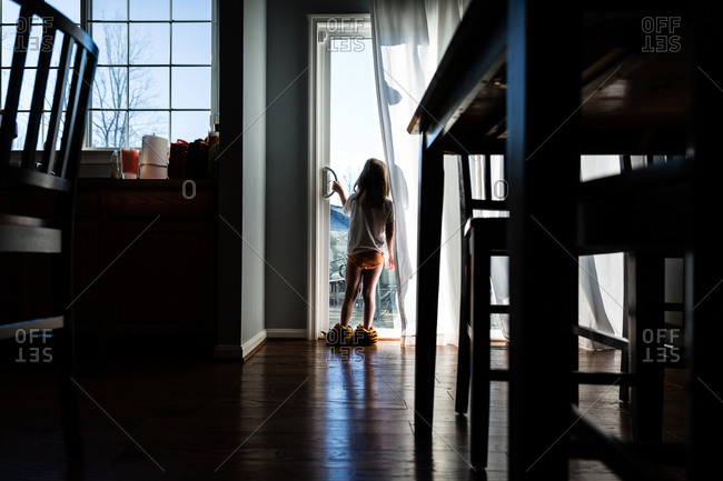Girl looking out a door