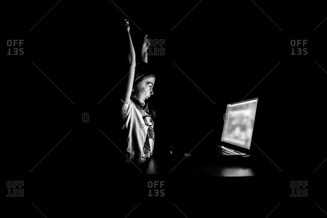 Girl cheering in front of a laptop