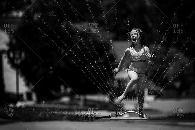 Girl jumping over a water sprinkler