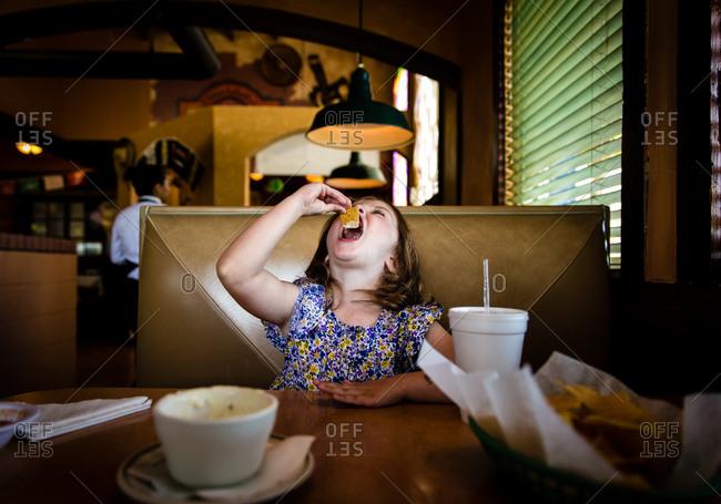 Girl eating tortilla chips in a restaurant