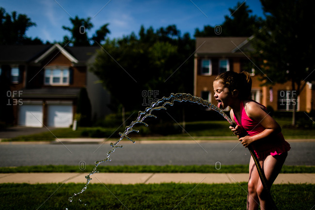 Girl drinking from a garden hose