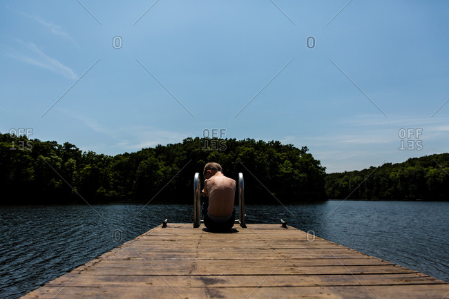 Boy sitting on the edge of a pier