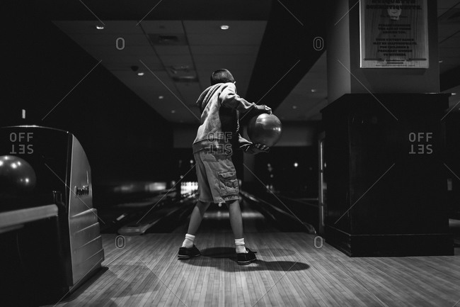 Boy about to throw a ball in a bowling alley