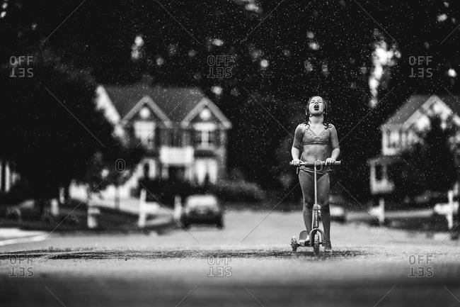 Girl standing in the summer rain