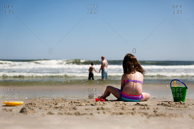 Girl playing in the sand on the beach