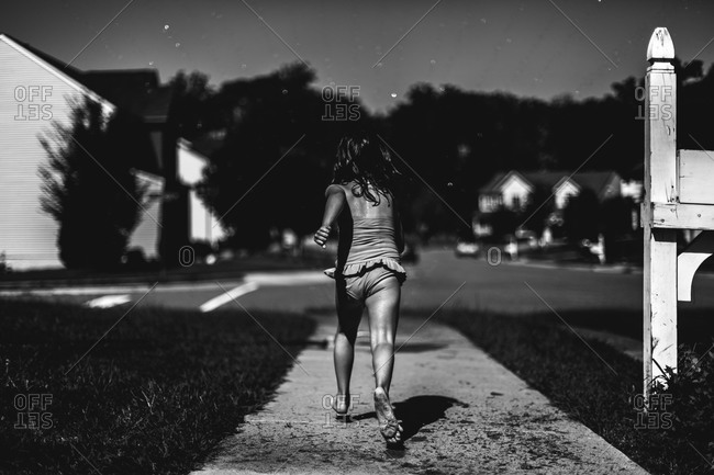 Back view of wet girl walking down the street