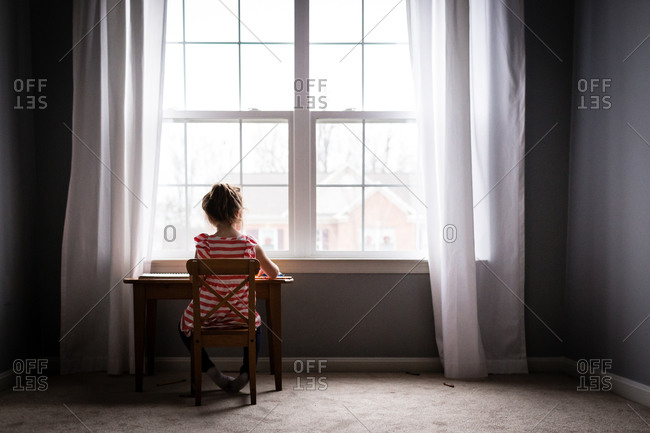 Girl drawing by the window