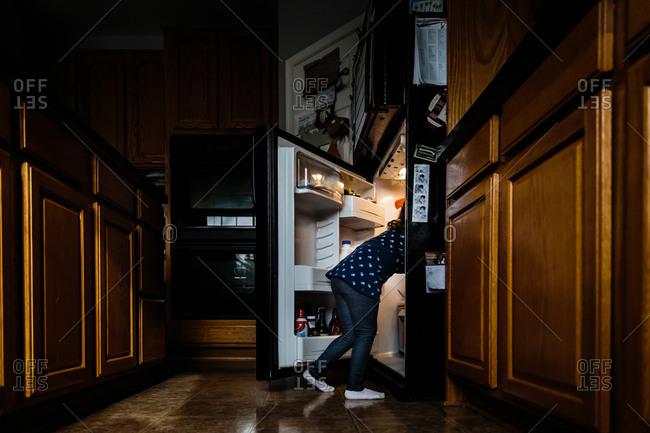 Girl rummaging through a fridge
