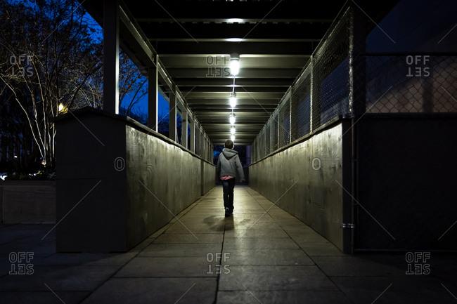 Boy walking down a street at night