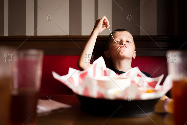 Boy eating pasta in a restaurant