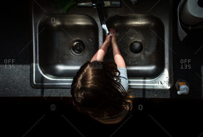 Girl washing her hands at the sink