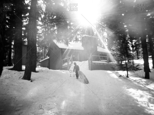 Child carrying a sled to snowy woodland cabin