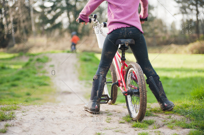 Girl on bike on rural path with boy