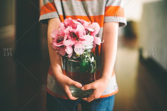 Boy carrying jar of flowers in hall