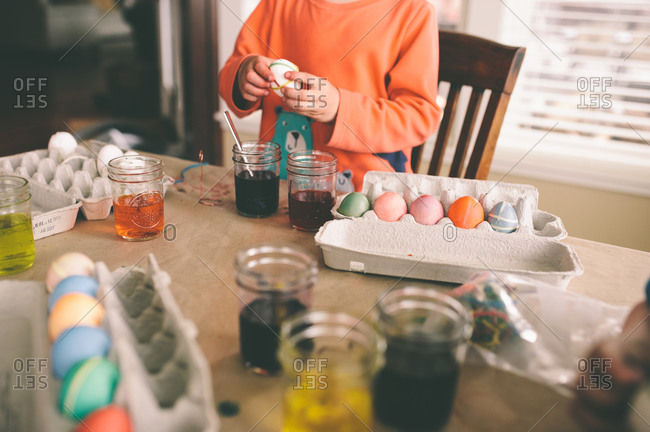 Child dying Easter eggs at a table