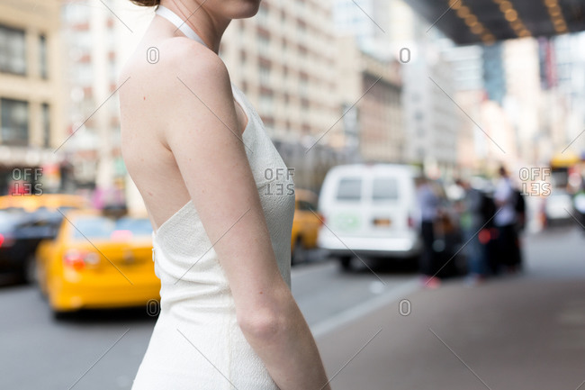 Woman in halter top gown in city street
