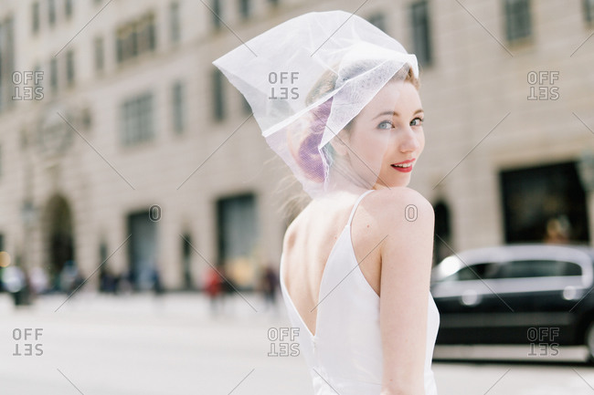 Portrait of woman in veil and dress in city street