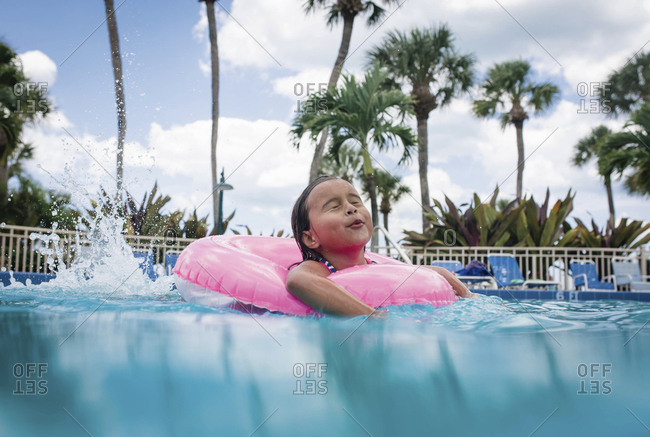 A little girl in an inflatable tube splashes in a pool