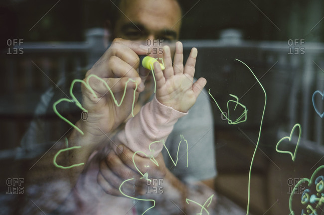 Man tracing young child's handprint on a window