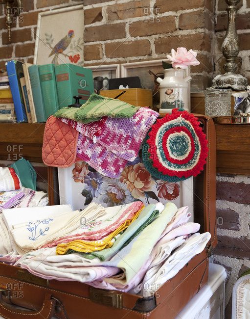 A suitcase filled with linens in a vintage shop