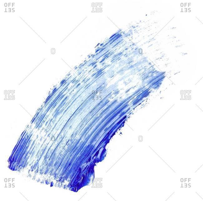 A swipe of blue mascara shot on white background
