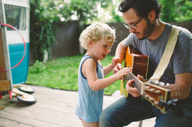 Father teaching his son about guitar playing