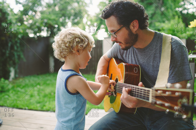 Father teaching his son about a guitar
