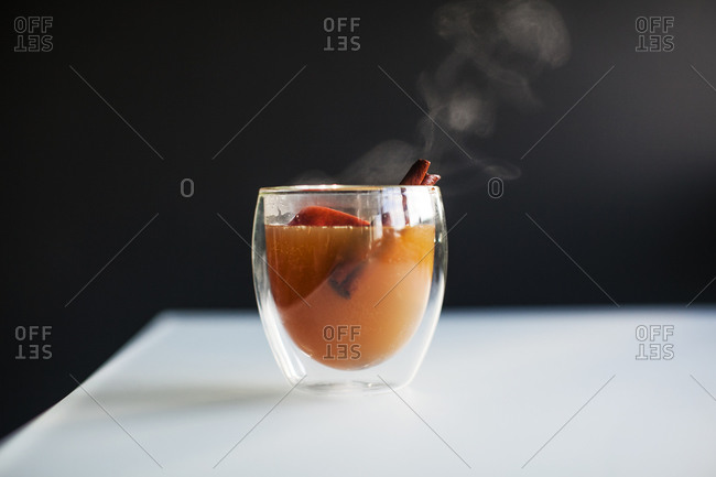 A steaming hot cup of apple cider with an apple slice and cinnamon stick