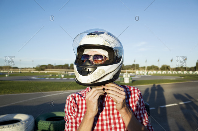 A young man buckles his helmet at a go kart track